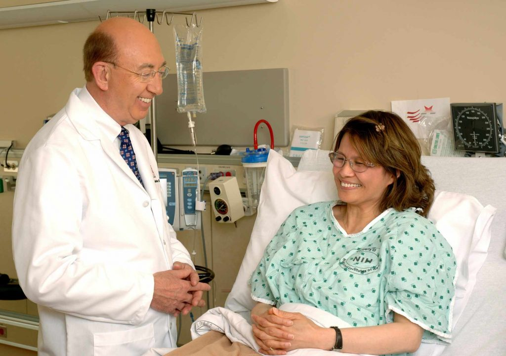 A male doctor consults with a female patient in a hospital bed